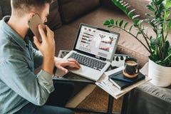 De jonge mens, gekleed in overhemd, zit thuis op laag bij koffietafel, gebruikt laptop met grafieken, grafieken, diagrammen op he stock foto's