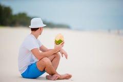De jonge mens geniet strand vakantie en het drinken van kokosnoot stock foto