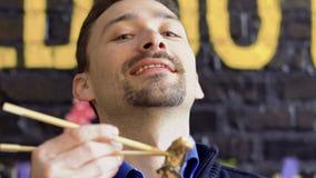 De jonge mens geniet van een geur van smakelijke pijlinktvis in beslag en adviseert schotel op camera stock footage