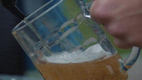 De jonge mens giet bier in een mok van een kraan stock footage