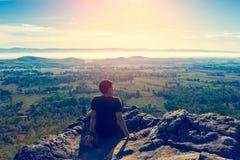 De jonge mens in groene sportkleding zit op cliff& x27; s rand Royalty-vrije Stock Foto's