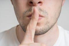 De jonge mens heeft vinger op lippen en het tonen stil gebaar zijn stock foto