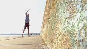 De jonge Mens heft Handen op en danst op een Riverbank met een Hoge muur in slo-Mo stock footage