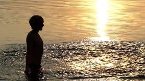 De jonge Mens heft Rivierwater in Palmen op en werpt het omhoog bij Zonsondergang stock video
