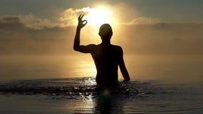 De jonge mens heft stromen omhoog van water in een meer bij zonsondergang in slo-mo op stock footage