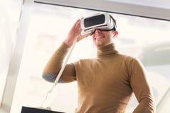 De jonge mens houdt 3D glazen in de opslag Stock Afbeeldingen