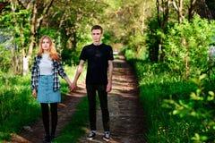 De jonge mens houdt de hand van zijn meisje, openlucht, zich bevindt op de weg Stock Foto