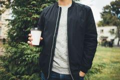 De jonge mens houdt een kop van koffie in zijn handen stock afbeeldingen