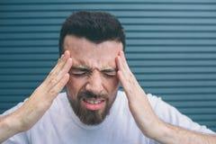 De jonge mens houdt handen op voorhoofd Hij heeft hoofdpijn De kerel voelt vreselijk Hij lijdt Geïsoleerd op gestreepte nad stock afbeeldingen