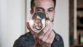 De jonge mens houdt kristallen bol voor gezicht stock foto's