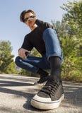 De jonge mens in jeans en tennisschoenen zit op de weg in het hout royalty-vrije stock foto
