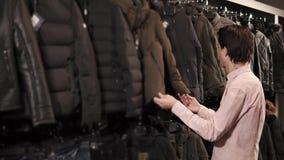 De jonge mens kiest een jasje in een kledingsopslag, bekijkt hij kleren op een hanger stock video