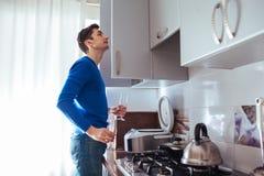 De jonge mens kijkt in de kast in de keuken royalty-vrije stock foto's