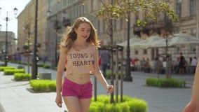De jonge mens koestert zijn gelukkige honing en gaat met een skateboard rijdend in de lente in slo-mo stock videobeelden