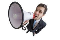 De jonge mens kondigt een bericht met megafoon aan Mening van hierboven Geïsoleerdj op witte achtergrond Royalty-vrije Stock Afbeeldingen