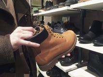 De jonge mens koopt of kiest de winterschoenen in schoenopslag stock foto's