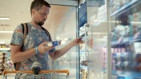 De jonge mens koopt yoghurt in een opslag
