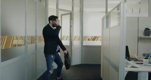 De jonge mens krijgt een nieuwe baan nadat hij heeft geïnterviewd, opgewekt en zeer gelukkig, de arbeider van bureau hem en begin stock videobeelden
