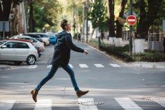 De jonge mens kruist de straat Stock Afbeelding