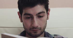 De jonge mens leest een boek en kijkt dan rond stock footage