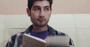 De jonge mens leest een boek en kijkt dan rond stock videobeelden