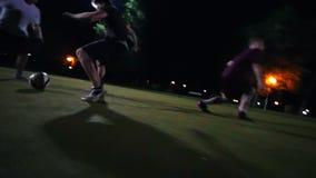 De jonge mens leidt de bal op een groen gebied, proberen andere spelers om zijn bal weg te halen stock video