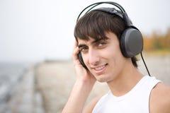 De jonge mens luistert aan muziek Stock Foto's