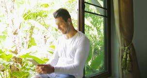 De jonge Mens luistert aan Muziek op Tabletcomputer met Oortelefoons Zittend op Venstervensterbank die aan Tropische Tuin kijken stock video