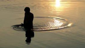 De jonge Mens maakt Cirkles in Rivierwateren en bekijkt Zonsondergang stock video