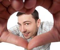 De jonge mens maakt het maken van hart ondertekenen Royalty-vrije Stock Fotografie