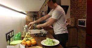 De jonge mens maakt zijn keuken schoon stock footage
