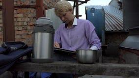 De jonge mens maakt zijn laptop op een bouwwerf schoon stock videobeelden