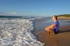 De jonge mens mediteert op strand in lotusbloem stelt Stock Foto