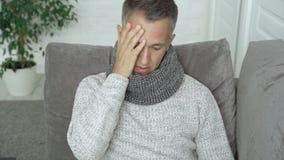 De jonge mens meet de temperatuurzitting op bank in huis Mannetje die ongelukkig tijdens een virus of een koude voelen stock videobeelden