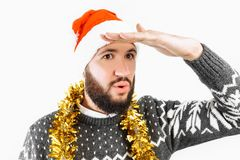 De jonge mens met een baard, een mens in een Santa Claus-hoed, onderzoekt de afstand, het komende Nieuwjaar stock foto