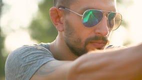 De jonge mens met een kanon poogt dichte omhooggaand te schieten stock video