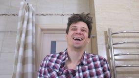 De jonge mens met een kater lacht bij zijn gedachtengang in de spiegel die zich in de badkamers bevinden stock footage