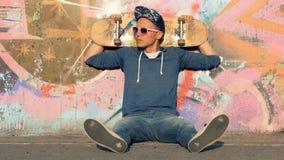 De jonge mens met een skateboard achter zijn hoofd zit op asfalt stock videobeelden