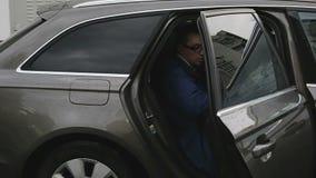 De jonge mens met glazen krijgt uit de achterdeur van de auto stock videobeelden