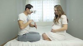 De jonge mens met glazen van virtuele werkelijkheid zit op het bed en toont een grote buik van zijn zwangere vrouw stock footage