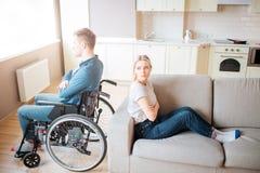 De jonge mens met handicap zit op rolstoel en bekijkt venster Debatteer en quirrel Kerel met speciale behoeften die achterover le stock afbeelding