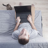 De jonge mens met laptop zit op de laag en de kat Hoogste mening royalty-vrije stock foto