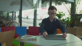 De jonge mens met netbook komt en zit bij de lijst in moderne bibliotheek stock footage