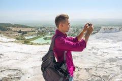 De jonge mens met rugzak, toerist, neemt beelden met zijn mobiel stock foto