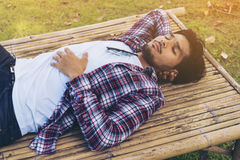 De jonge mens neemt dutje op bamboebed of zetel Royalty-vrije Stock Fotografie