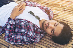 De jonge mens neemt dutje op bamboebed of zetel Stock Foto's