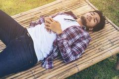 De jonge mens neemt dutje op bamboebed of zetel Stock Fotografie