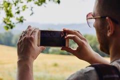 De jonge mens neemt foto van landschap gebruikend een smartphone stock afbeelding