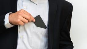 De jonge mens neemt leeg adreskaartje van de zak van zijn s stock foto