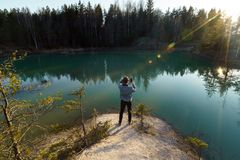 De jonge mens neemt reisfoto's - Mooi turkoois meer in de stijlkleuren van Letland - Meditirenian-in Baltische staten - royalty-vrije stock afbeelding